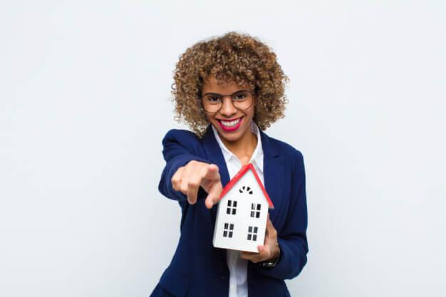 indicadores imobiliadrios mulher segurando uma mini casa e apontando
