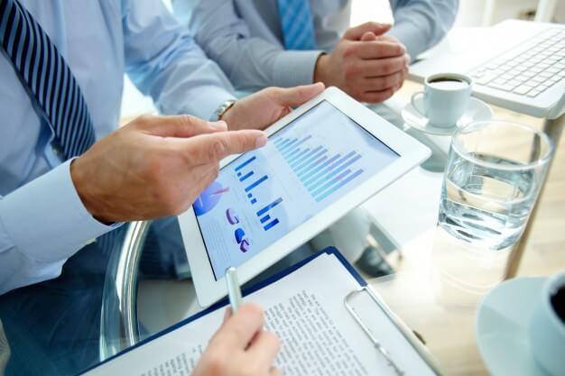 simulador de investimento homens analisando graficos no tablet
