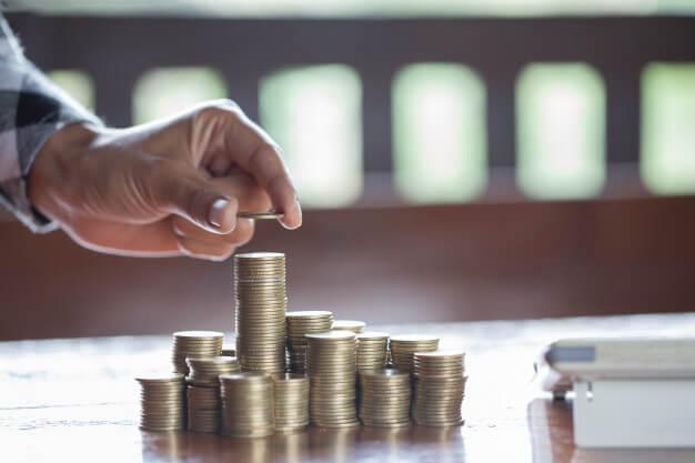pessoas mais ricas do mundo empilhando moedas